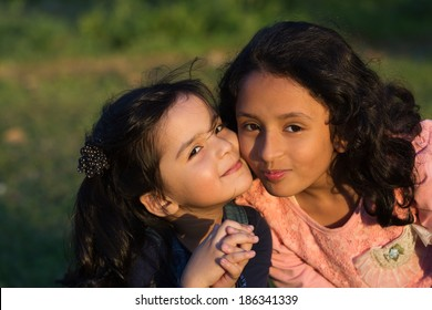 sisters love,close up of little girl kissing her younger sister