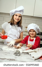 Sisters making dough in white kitchen. Happy family in making cookies at home. Happy kids cooking healthy meal in the white kitchen.