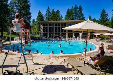 Sisters, Oregon - 7/20/2019: People swimming and sun bathing at a swimming pool at Black Butte Ranch near  Sisters, Oregon