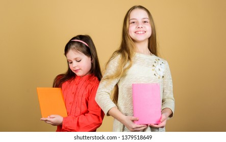 Sisters pick books to read together. Adorable girls love books. Secret diary or personal journal. Smart is great. Kids girls with books or notepads. Education and kids literature. Favorite fairytale.