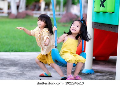 Sisters play happy swings. Older sister swing and run to the side. Brethren play together on the playground. Cute girl was excited when the swing was swaying. Baby kid is 3-5 years old.