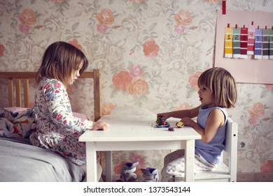 sisters play together in a real room, gray toning and lifestyle
