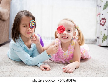sisters playing with delicious lollipops