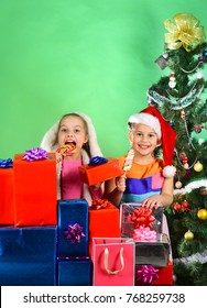 Sisters in Santa Claus hats stand behind gift boxes. Girls celebrate Christmas, have fun. Childhood and leisure concept. Children with smiling faces stand under Christmas tree on green background.