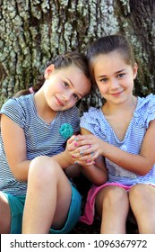 Sisters sit with clasped hands.  Their finger nails show different colors signifying and different personalities.  With hands clasped, they bind together in friendship.