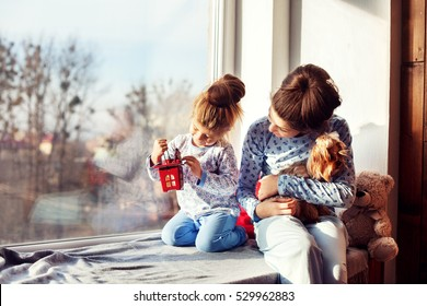 sisters sitting on the windowsill with the dog. The concept of Christmas
