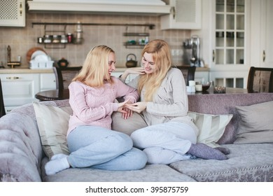sisters sitting together on a couch in the dining room