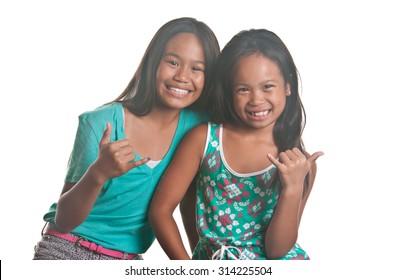 Sisters smile with a shaka gesture to show Aloha