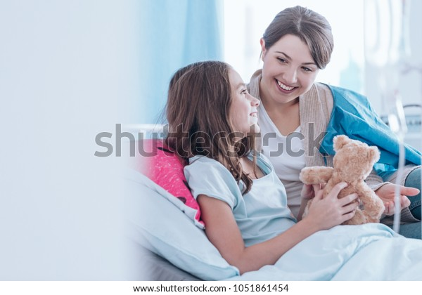 Sisters smiling and lying in bed in the hospital together. Family support during illness concept