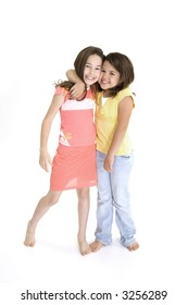 Sisters standing on white background smiling wearing casual clothes