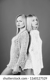 sisters twins, two pretty girls or women or fashionable models with long, blond hair and stylish makeup posing in sexy, knitted sweaters on red background. Family love, sisterhood. Relationship