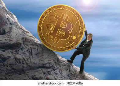 Sisyphus concept showing man struggling to push giant Bitcoin up a mountain representing goal of mining and getting rich with this new peer to peer monetary system hoping that it's value goes up.