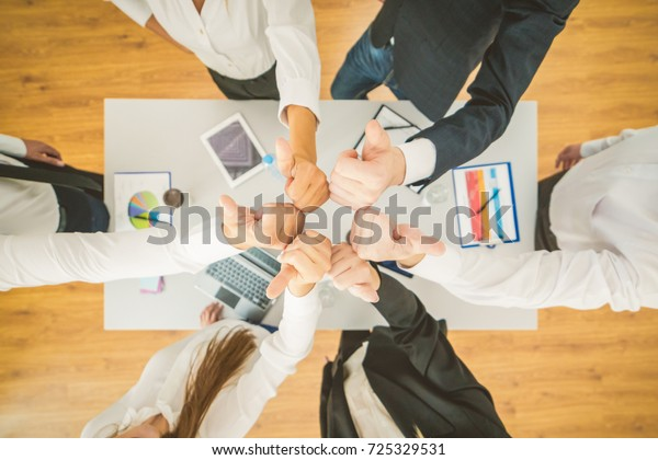 The sit business people thumb up near the desktop. view from above