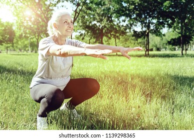 Sit down. Cheerful enthusiastic elderly woman bending her knees while exercising in a park