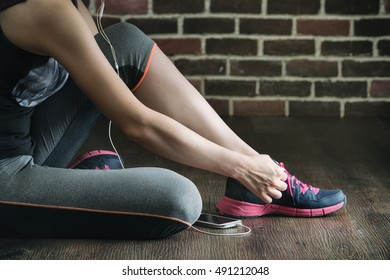 sit down tie sneakers shoestring listening to music before fitness exercise, gym sport healthy lifestyle