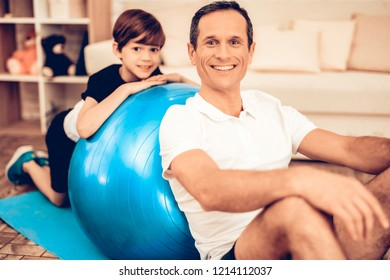 Sit on Floor with Fitball. Sport at Home. Gym Mat. Doing Sports. Man and Boy Train at Home. Health Concept. Healthy Lifestyle. Swiing Press on Floor. Man and Boy with Fitball. Swing Press on Fitball.