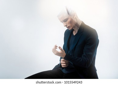 Sit and think. Concentrated sad stylish man sitting in the bright room looking at hands and thinking.