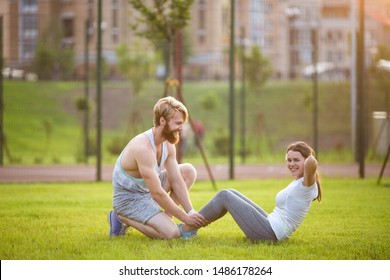 Sit ups fitness couple exercising sit up outside in grass. Fit people working out cross training. Woman doing abdominal crunches press exercise with trainer. Couple Doing Sit-Ups Abdominal Crunch.