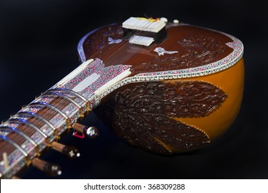 Sitar, a String Traditional Indian Musical Instrument, close-up, blue lens effect. dark background. Evening of ethnic oriental music. Indian Raga