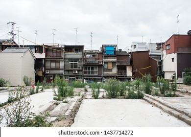 The site of demolished building with weeds in an old town houses area, Hiroshima, Japan. There is the foundation of building or demolished building site in front of viewer.
