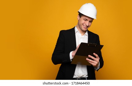 Site manager. Close-up photo of a professional engineer in formal clothes and helmet, who is writing something on his plan.