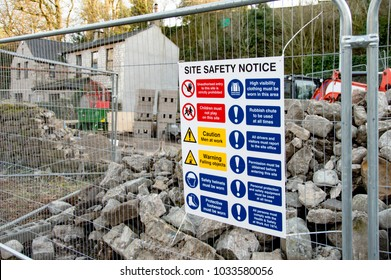 """""""Site Safety Notice"""" Sign Attached To Metal Fence In Front Of Building Site"""