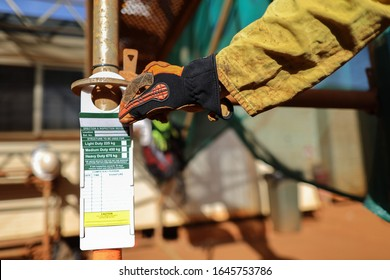 Site scaffolder supervisor hand wearing safety CS5 glove protection inspecting scaffolding tag label on standing tube ensure its safe up to date prior used  on construction site