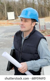 Site supervisor with security helmet standing on construction site