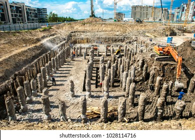 Site with workers. Concrete building construction. Construction site with construction workers. Concrete piles for building foundation. Site with construction machinery, concrete piles and workers