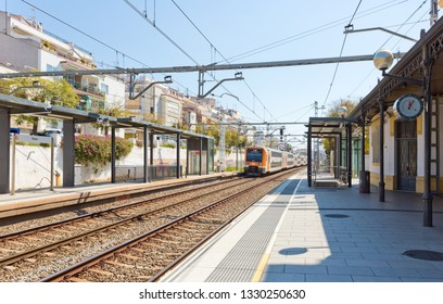 Sitges, Spain - March 5, 2019: A passenger train approaches the Sitges train station.