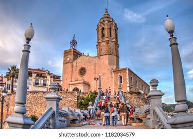 SITGES, SPAIN - SEPTEMBER 24, 2015: Tourists visit the Sitges Town Hall and Church Parish of Saint Bartholomew and Santa Tecla in small resort town Sitges, in the suburbs of Barcelona.
