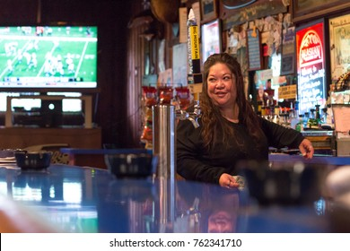 Sitka, Alaska, USA - August 20, 2017: A female bartender working at a traditional american bar - saloon in Sitka, Alaska.