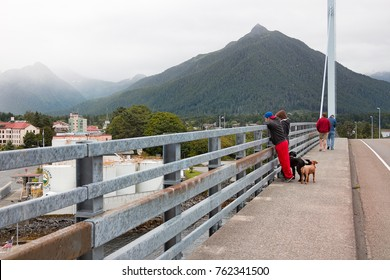 Sitka, Alaska, USA - August 21, 2017: People looking the view on the sidewalk of the John O'Connell cable-stayed bridge, Sitka.