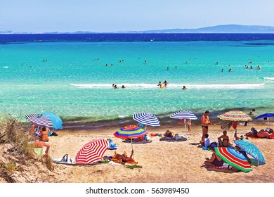 Sitonia, Greece - July 02, 2012: people sunbathing and swimming on the beach of the Aegean sea