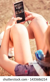Sitting alone. Attentive young girl in shorts resting on the bare ground while listening to music in smartphone app
