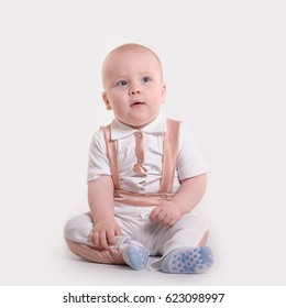 Sitting baby boy in white suit looking upwards on white background
