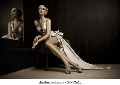 Sitting beautiful woman beside mirror