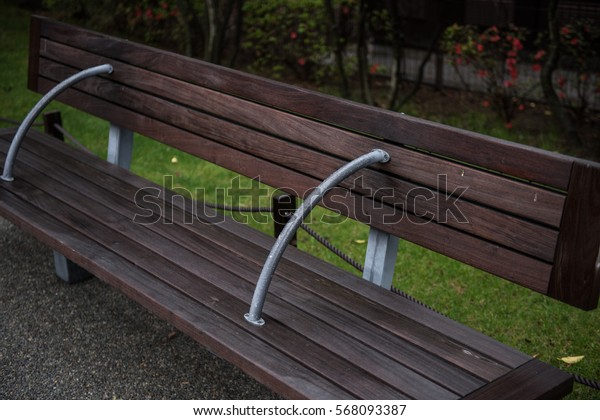 A sitting bench made of wood is seen on the picture inside a park. On the background, the lush greeneries of the park is seen too on a cloudy day.