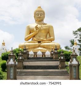 A sitting Buddha statue against a blue sky.