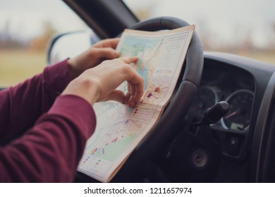 sitting in the car driver hands holding the map and searching the way out, lost in forest