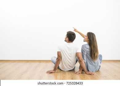 The sitting couple look the empty wall and gesture