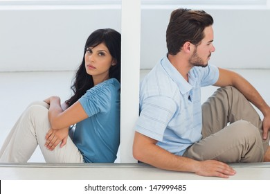 Sitting couple are separated by wall with woman looking at camera