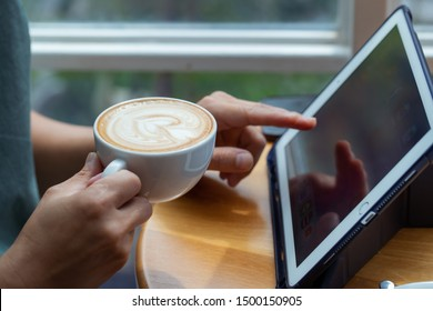 Sitting and drinking coffee while playing the iPad
