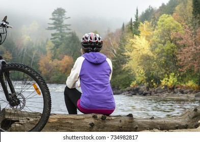 sitting female bicyclist admires beautiful autumn landscape in foggy morning during halt at sand beach of riviere-rouge river by corridor aerobique bicycle trail in province of quebec, canada