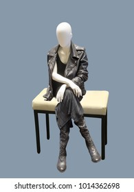 Sitting female mannequin wearing leather jacket, isolated.  No brand names or copyright objects.