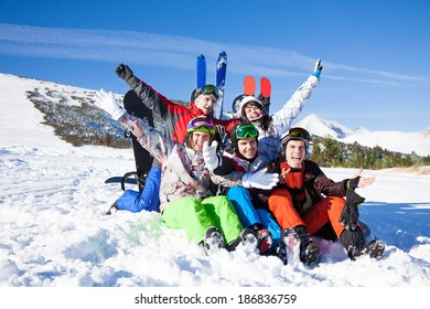 Sitting friends with snowboards lifting hands up