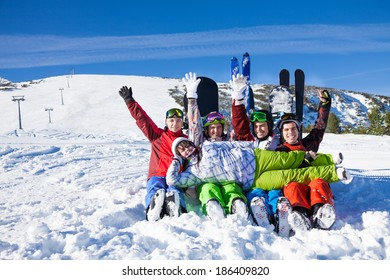 Sitting happy friends with snowboards having fun