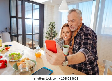 Sitting in kitchen. Mature couple of businessmen posing for photo while sitting in the kitchen