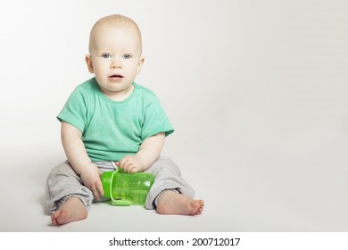 Sitting little cute baby with feeding bottle isolated on white background