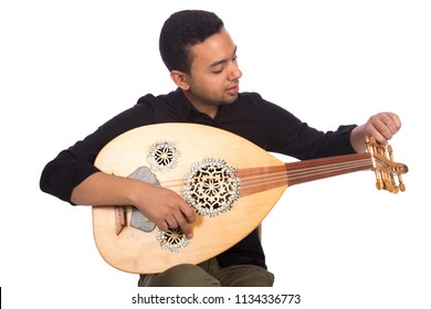Sitting musician adjusts the strings of the lute to play music smiling, isolated on a white background.